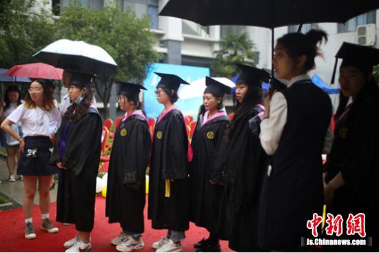 毕业生们冒雨参加毕业典礼。中新社记者 泱波 摄