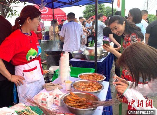 生态虾品鉴会上,当地民众驻足免费品尝。 崔佳明 摄