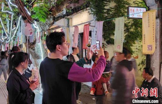 南长街和小娄巷内悬挂了上万条灯谜,吸引了众多市民参与。 孙权 摄