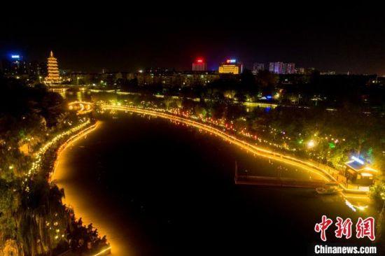 14日晚,千年凤城河河面,被夜钓者点亮。 汤德宏 摄