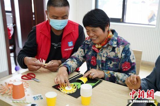 中建三局南京尧化门项目在南京尧辰社区教老人们制作工艺品。(董瑾 摄)