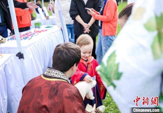 """来自海内外的千余名游客和市民身着汉服登高""""辞青""""、赏菊花、插茱萸、品文化。南京旅游集团供图"""