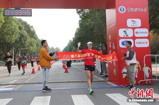 半程马拉松赛女子组第一名冲过终点线。张驰 摄