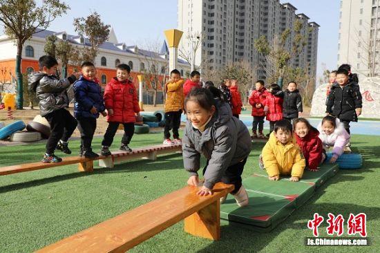 孩子们在操场上玩走平衡木游戏。顾建 摄