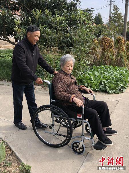 周汉龙用轮椅推着养母散心。射阳县文明办供图