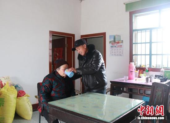 周汉龙悉心照顾养母。射阳县文明办供图
