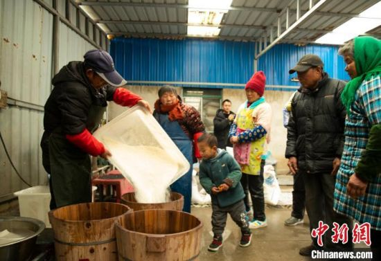村民将米粉装蒸桶。 汤德宏 摄