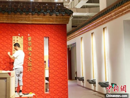 """施工人员在""""紫禁城与大运河""""展馆进行内装修。 崔佳明 摄"""