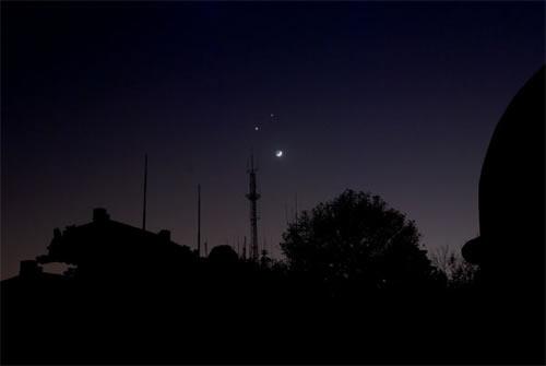弯弯的月亮上方镶嵌着两颗星星,宛如夜空里一张巨大的笑脸