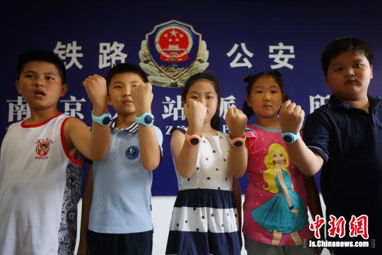 8月15日,孩子们展示具有定位和报警功能的智能手环。中新社记者 泱波 摄