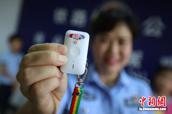 南京铁路民警展示为孩子们配发的具有定位和报警功能的钥匙链。中新社记者 泱波 摄