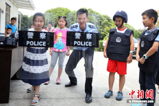 孩子们参观警用装备并互动,增强安全防范知识。中新社记者 泱波 摄