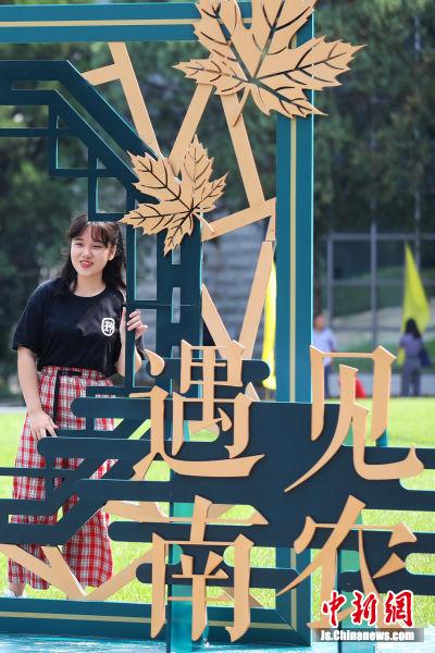 """大学生在""""遇见南农""""字样旁留影。 中新社记者 泱波 摄"""