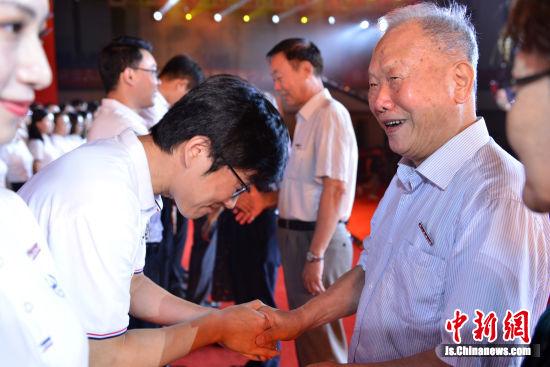 离退休教师代表为新入职教师代表佩戴校徽。王爽 摄