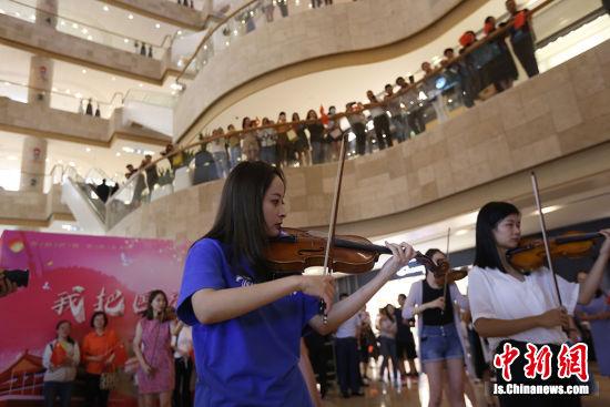 悠扬的小提琴声拉开公益快闪序幕。泱波 摄