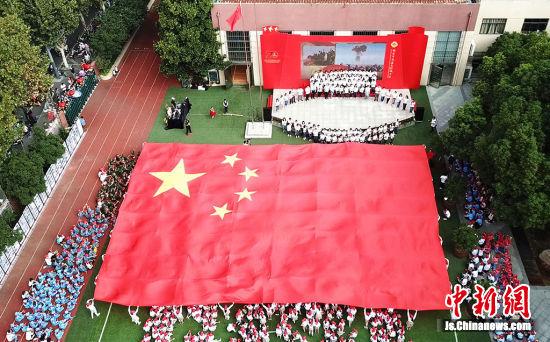 当一幅长24米、宽16米,由81位同学手执一角的巨幅红旗在操场上徐徐展开时,两千余名师生的歌声响彻凤凰园上空。
