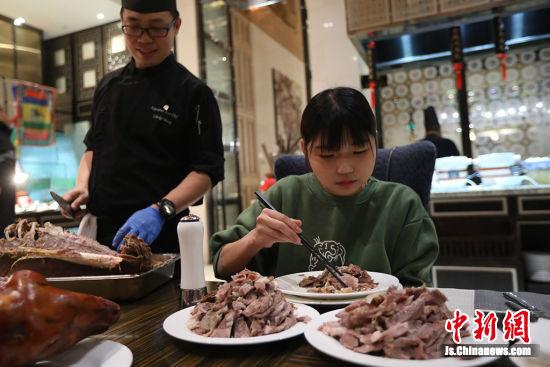 厨师在旁边切肉,小楠安静的吃肉。泱波 摄