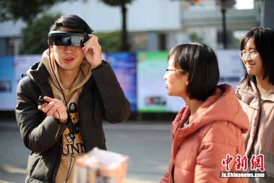 """大学生体验""""迁移眼镜""""。中新社记者 泱波 摄"""