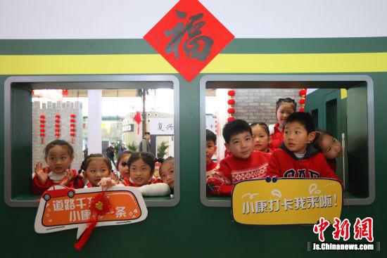 """孩子们在高铁南京南站设置的""""小康照相馆""""内拍摄照片。中新社记者 泱波 摄"""