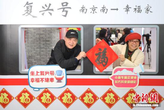 """两名旅客在高铁南京南站设置的""""小康照相馆""""内拍摄照片。中新社记者 泱波 摄"""
