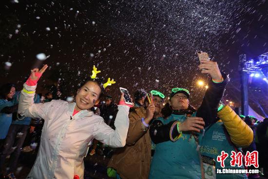 """参与者在""""人工降雪""""处留影。 中新社记者 泱波 摄"""