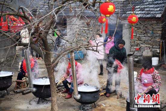 村民忙着大锅烧肉烧鱼。 桂宝林 摄